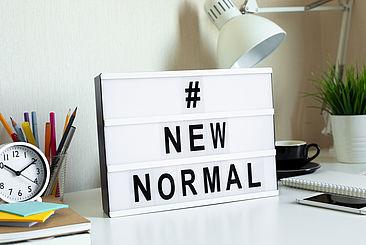 """Arbeitsplatz mit einem Schild, auf dem """"The new normal"""" steht"""