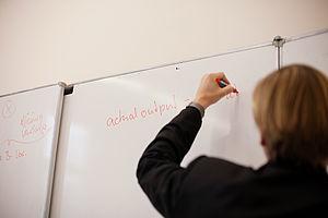 Hochschullehrer schreibt etwas an die Tafel