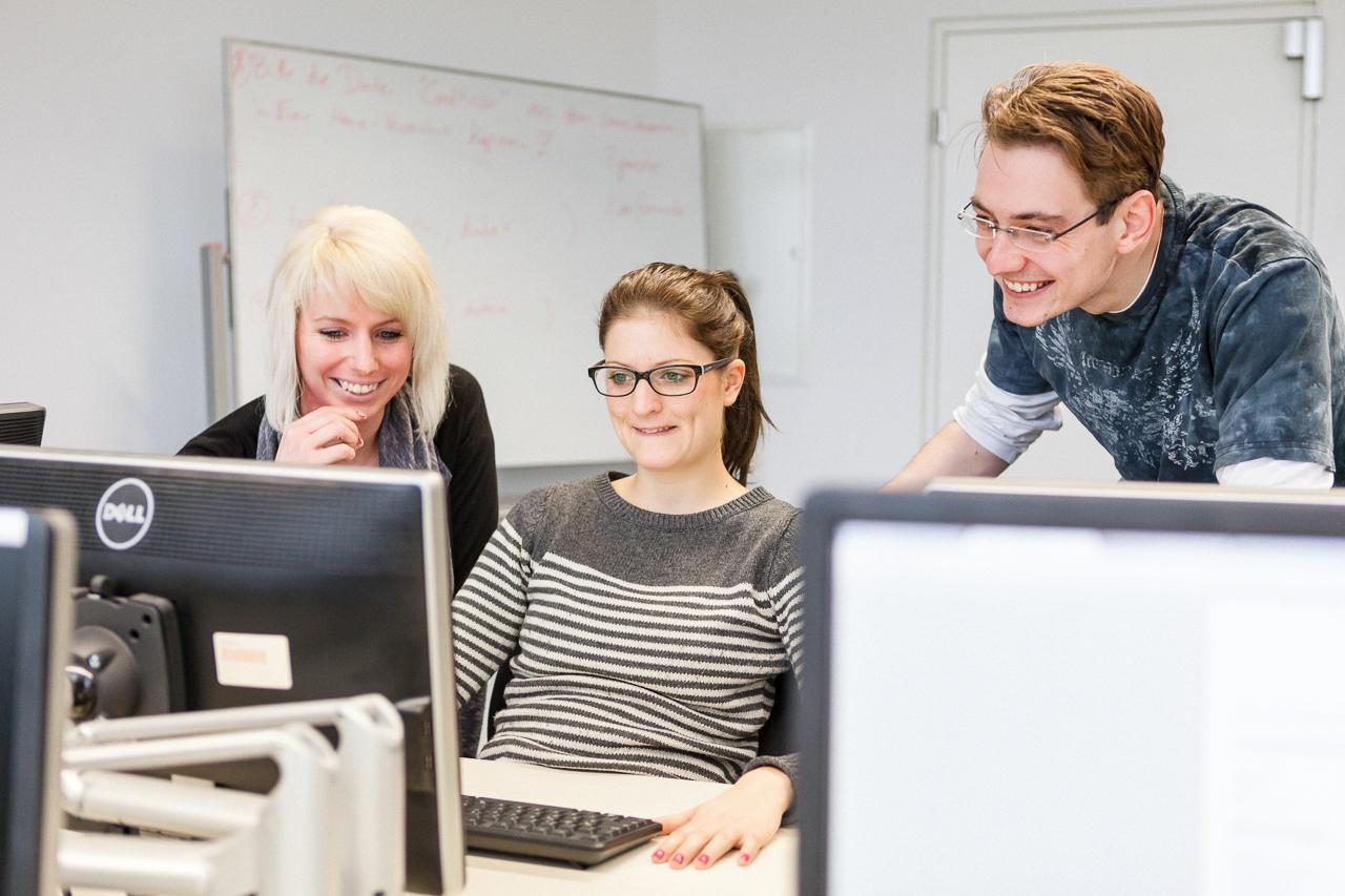 Drei Studierende des Wirtschaftsingenieurwesens an einem PC